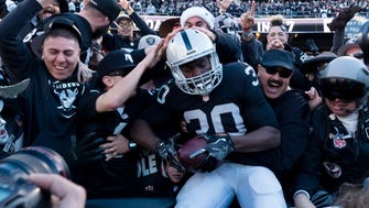 Oakland Raiders running back Jalen Edwards (30) leaps into the stands to celebrate with fans after a touchdown against the Indianapolis Colts during the second quarter at the Oakland Coliseum.