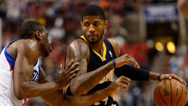Indiana Pacers forward Paul George (24) is defended by Philadelphia 76ers forward Thaddeus Young (21) during the third quarter at the Wells Fargo Center, March 14, 2014.