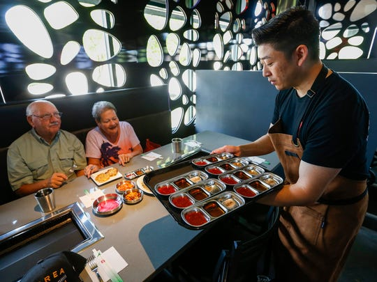 Cosmo Kwon, center, co-owner of Bawi, serves a group of Korean War veterans a selection of dipping sauces during a special event at the new all-you-can-eat Korean barbecue restaurant.