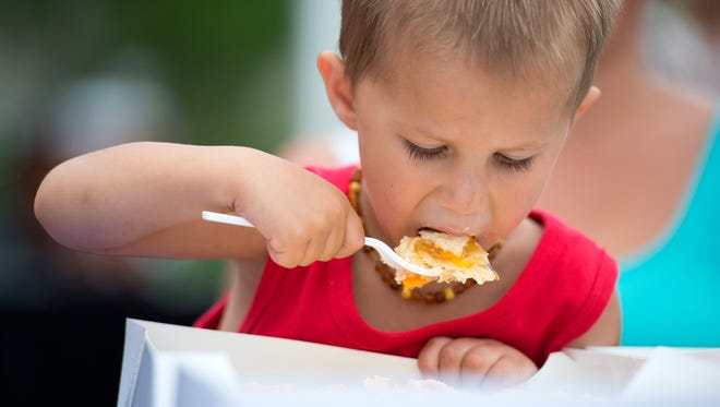 Peter Hickox, 3, eats a peach pie during the pie-eating contest at the Fort Collins Peach Festival at Hughes Stadium Saturday, August 23, 2014.