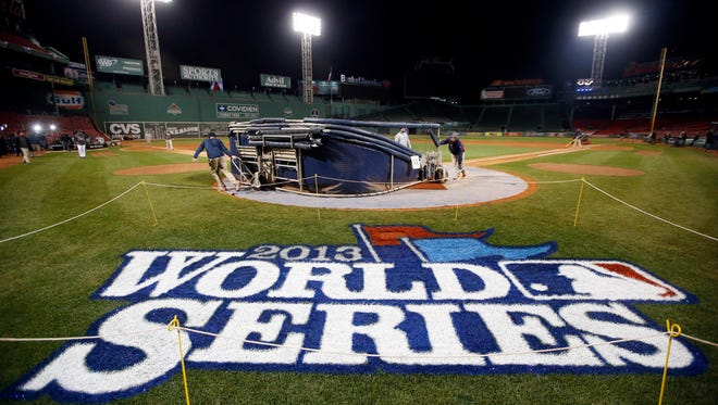 Grounds crew members dismantle the batting cage after the Boston Red Sox's workout at Fenway Park in Boston on Tuesday.