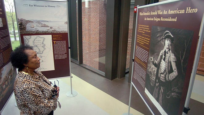 Lottie B. Scott, a member of the Norwich Historical Society, examines an exhibit on Revolutionary War General Benedict Arnold in the Slater Museum, at Norwich Free Academy, in Norwich, Conn. The exhibit tells the story of Arnold leading his Naval fleet into battle with the British on Valcour Island in October 1776.