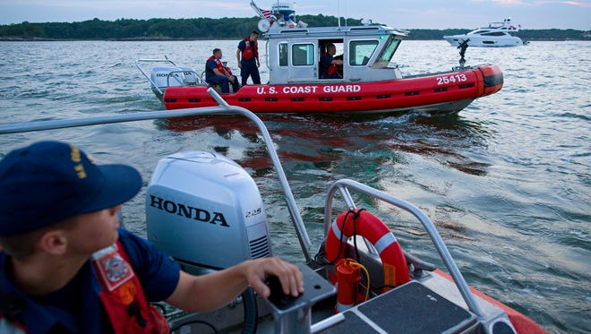 U.S. Coast Guard response boats out of Station Kings Point, N.Y., patrol near Glen Island in western Long Island sound near New Rochelle, N.Y. as they work to keep boaters at a safe distance from barge that would soon be the water base of a fireworks display. A wedding celebrated on Glen Island featured fireworks, and the Coast Guard engaged in keeping a safe zone for boaters around the pyrotechnics.