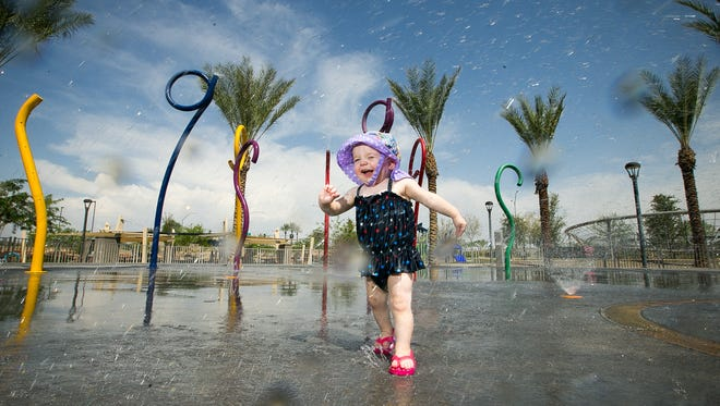Mailey Swanson, 1, plays on the splash pad at Riverview Park in Mesa on Friday, July 25, 2014.