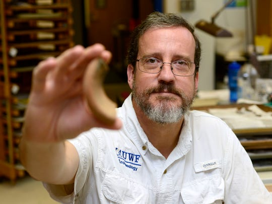 John Worth, associate professor of historical archaeology with UWF Department of Anthropology, holds up a sherd from a mid-16th century olive jar found at a recently discovered historic site that is the oldest established European multi-year settlement in the United States. The site was discovered in October by local historian Tom Garner when it was uncovered by residential construction.