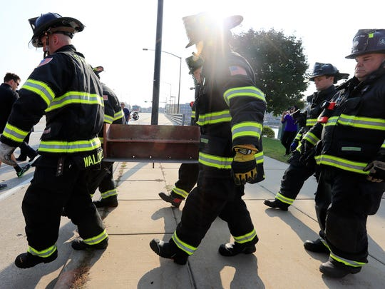 Green Bay firefighters remove the metal beam from the