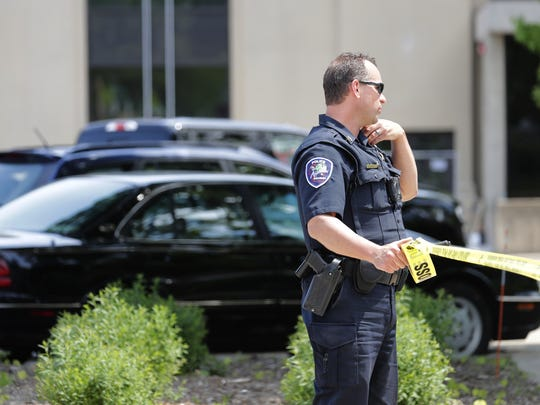 Sgt. Adam Konkle, of the Appleton Police Department, ropes off an area in front of the Outagamie County Administrative Building along South Walnut Street after a suspicious briefcase was found on the sidewalk Tuesday.