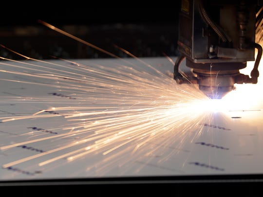 A laser cutter is shown in operation at American-3
