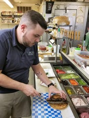 Chef Jared Bradley loads a sandwich with the meat, house tzatziki and fresh veggies before wrapping the pita and sending it forth to the happy diner.