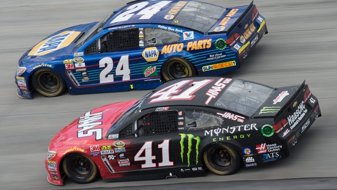 Chase Elliott (car #24) and Kurt Busch (car #41) race around turns one and two in the NASCAR Sprint Cup Series AAA 400 Drive for Autism race at Dover International Speedway in Dover, Del.