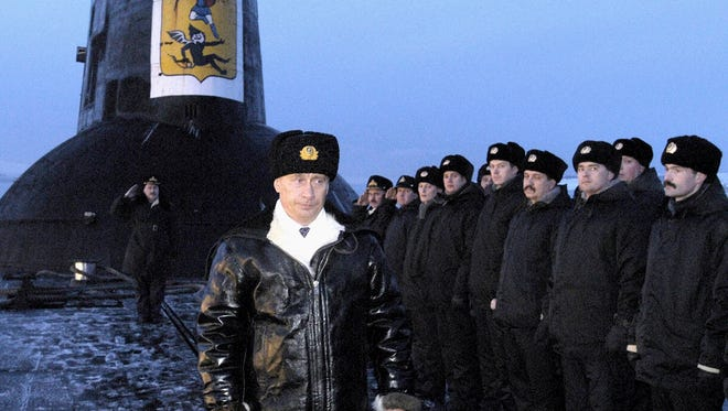 In this file photo taken on Feb. 17, 2004, Russian President Vladimir Putin thanks the crew of the Arkhangelsk nuclear submarine in the Barents Sea, Russia.