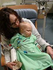 Magen Lowrance holds her son, Aiden, after his open-heart surgery.