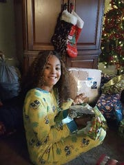 Keyera Malick opens a Christmas present made possible by a generous Asbury Park Press reader.