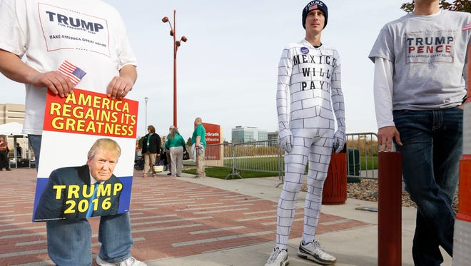 Kevin Lake of Jefferson, Iowa (right) wears a border wall outfit he bought online Friday, Oct. 28, 2016, as he waits to get into a campaign rally for Republican presidential candidate Donald Trump at McGrath Amphitheatre in Cedar Rapids.