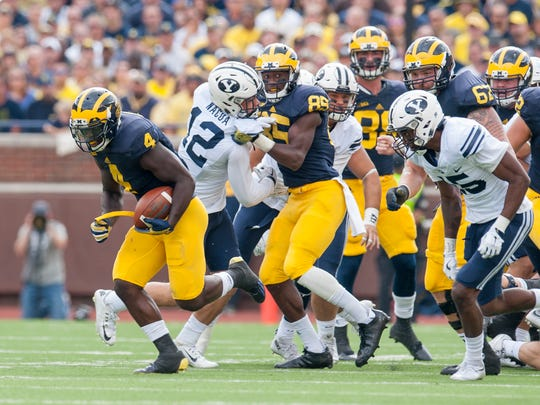 Michigan running back De'Veon Smith, left, emerges from a pile to run for a 60-yard touchdown in the second quarter.