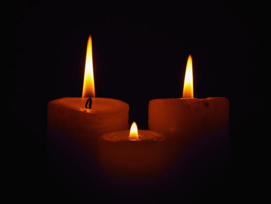 Three burning candles in the darkness