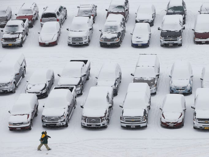 A fan makes his way to Lambeau Field in the snow before