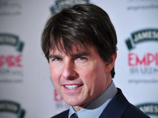 US actor Tom Cruise poses for pictures as he arrives for the 2014 Empire Awards in central London on March 30, 2014. AFP PHOTO / CARL COURTCARL COURT/AFP/Getty Images