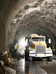 Construction crews spray gunite on the tunnel's ceiling
