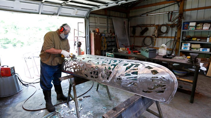 From an old canoe, an Ozarks man creates art with a torch