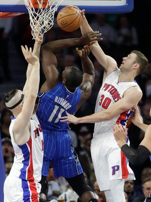 Pistons forward Jon Leuer (30) swats the ball away from Magic center Bismack Biyombo (11) during the first half Friday at the Palace.