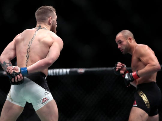 Conor McGregor, left, taunts Eddie Alvarez during a lightweight title mixed martial arts bout at UFC 205, early Sunday, Nov. 13, 2016, at Madison Square Garden in New York. McGregor won the bout. (AP Photo/Julio Cortez)