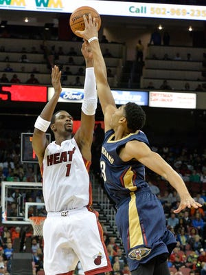 Miami Heat's Chris Bosh, left, has his shot blocked by New Orleans Pelicans' Anthony Davis during the first quarter of an NBA basketball preseason game in Louisville, Ky., Saturday, Oct. 4, 2014. (AP Photo/Timothy D. Easley)