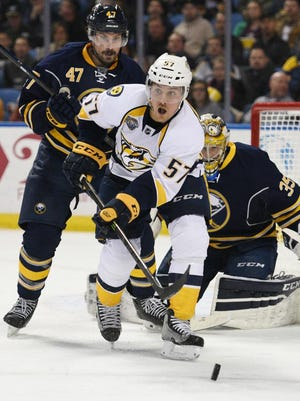 Buffalo Sabres defenseman Zach Bogosian (47) and goaltender Linus Ullmark (35) keep an eye on Predators right winger Gabriel Bourque (57) as he chases a rebound during the second period.
