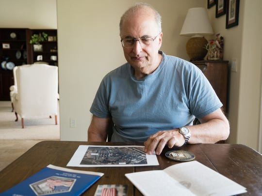 Bob Proodian looks at a photograph of The Pentagon in his home in Rancho Mirage, Calif., Aug. 18, 2016, as he reflects on his experience of working in the Pentagon on Sept. 11, 2001.
