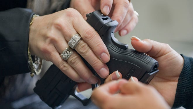 A client at a gun shop is shown the safety features of a handgun.