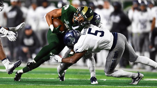Wolf Pack safety Dameon Baber tackles Colorado State wide receiver Olabisi Johnson during a game in Fort Collins, Colo.