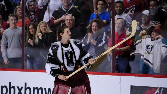Apr 11, 2015: Arizona Coyotes goalie Mike Smith (41) throws a stick to the crowd after the game against the Anaheim Ducks at Gila River Arena.