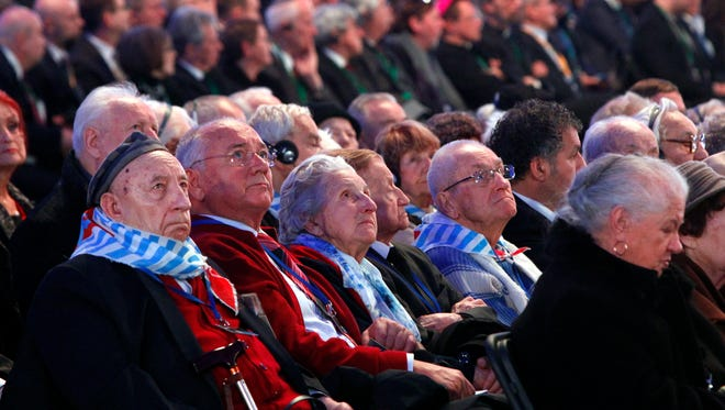 Holocaust survivors watch suspended screens in a tent raised at the entrance of the Birkenau Nazi death camp in Oswiecim, Poland, Tuesday, Jan. 27, 2015, during the official remembrance ceremony. About 300 survivors gathered with leaders from around the world to remember the 1.1 million people killed at Auschwitz-Birkenau and the millions of others killed in the Holocaust. (AP Photo//Czarek Sokolowski)
