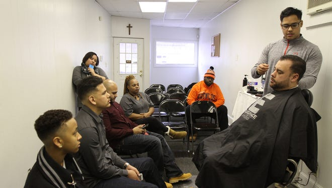 Gil Vargas presents trimming and razor techniques to students and other barbers at Young & Gifted Global Ministries on East Main Street. Richard C. Johnson started a seminar to help young barbers learn tips from each other. Johnson said he has seen many young barbers go out of business and wants to help them succeed.