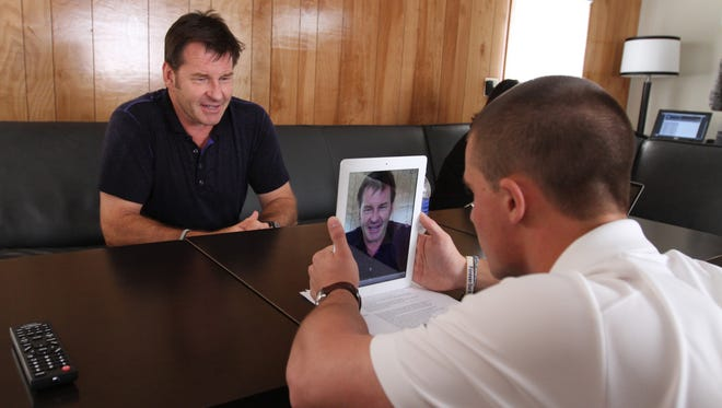 Sir Nick Faldo does a quick interview for CBS Sports television 's website with social media intern Andrew Kristy of Fairport during the  95th PGA Championship at Oak HIll Country Club in Pittsford in 2013.