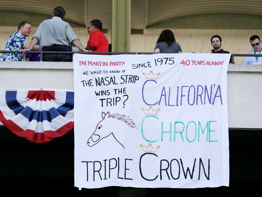 Fans gather near a sign supporting race horse California Chrome at Belmont Park, Saturday, June 7, 2014, in Elmont, N.Y. California Chrome is the favorite to win the Belmont Stakes horse race and Triple Crown later in the day. (AP Photo/Seth Wenig)