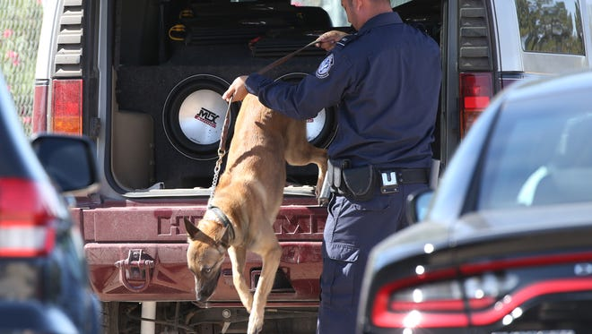 A Customs and Border Protection officer leads his dog on a search of an SUV in this El Paso Times file photo. Two dogs on loan to law enforcement officials in the Texas Gulf Coast were allegedly strangled to death by a suspected undocumented immigrants.