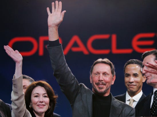 Larry Ellison, center, smiles with now-Oracle  co-CEO