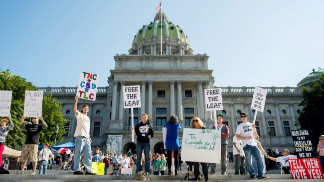 Supporters raise signs during a rally in support of a bill to legalize medical marijuana on the steps of the state Capitol building in Harrisburg in 2014.
