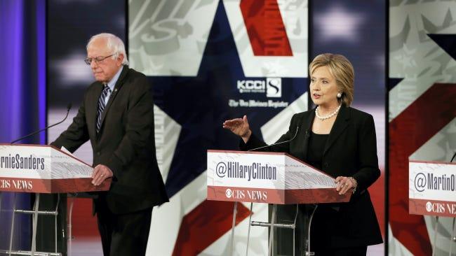 Hillary Rodham Clinton talks as Bernie Sanders listens during a Democratic presidential primary debate, Saturday, Nov. 14, 2015, in Des Moines, Iowa. (AP Photo/Charlie Neibergall)