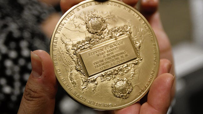 Diane Rogge holds her husband's Carnegie Medal  at the National Guard Armory in Farmington, New Mexico, in this file image from July 12, 2014.