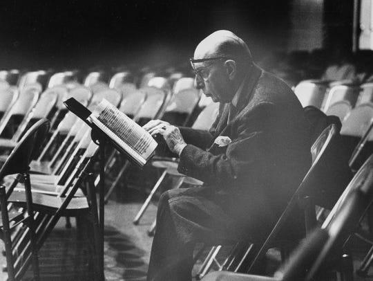 Wearing two pairs of eyeglasses, Igor Stravinsky follows