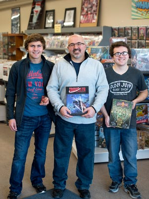 Kevin Knight, owner of Knight's Comics & Games, center, holds one of his favorite books, the Traveller Core Rulebook, with his sons Keaghan, left, and Kelric, right, at his store in Henderson, Ky., on Saturday, Nov. 11, 2017.