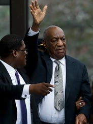 Bill Cosby gestures as he departs the Montgomery County