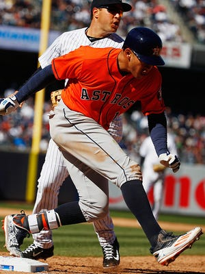 Carlos Correa of the Houston Astros beats out a throw to first base missed by Mark Teixeira of the New York Yankees in the eighth inning during Opening Day at Yankee Stadium on April 5, 2016 in New York City.