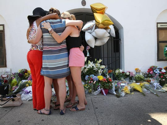 People hug as they pay their respects in front of Emanuel AME Church on June 18 in Charleston, S.C. Nine people were killed in a mass shooting during a prayer meeting at the church.