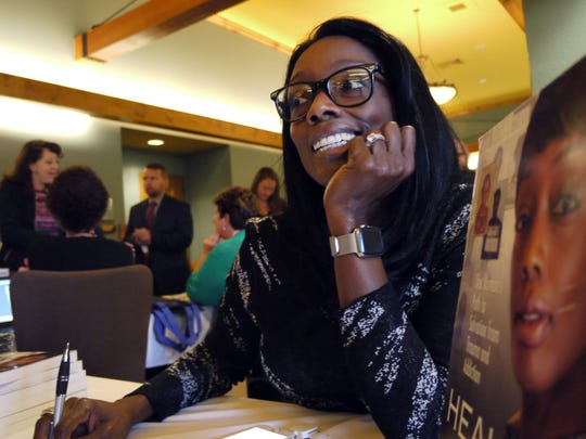 Tonier Cain signs copies of her autobiography, Healing Neen, during a statewide conference in the Wisconsin Dells, Wis., on using trauma-informed care to help children overcome adverse childhood experiences. A former homeless crack addict, Cain travels the world advocating the use of trauma-informed care to help children and adults heal from negative experiences.