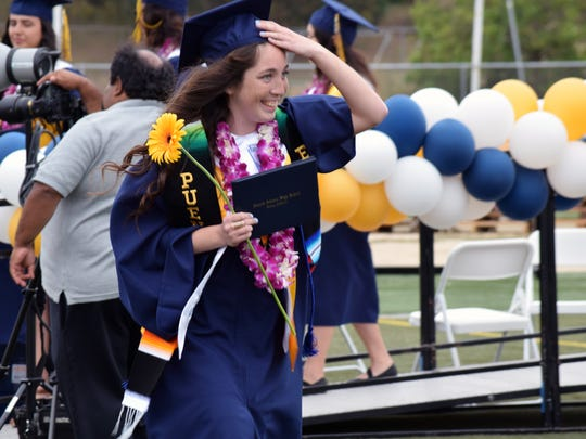 A senior walks off with her diploma.