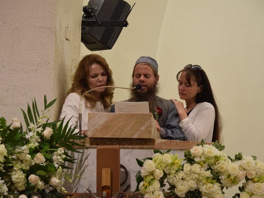 Kenny Irwin Jr. reads from the Quran, with support from his sisters, during Catholic Mass at Our Lady of Solitude in Palm Springs on Wednesday, July 6, 2016.