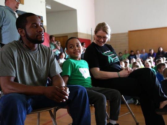 Trayson Harrell, middle, looks at his dad, Eric Harrell,